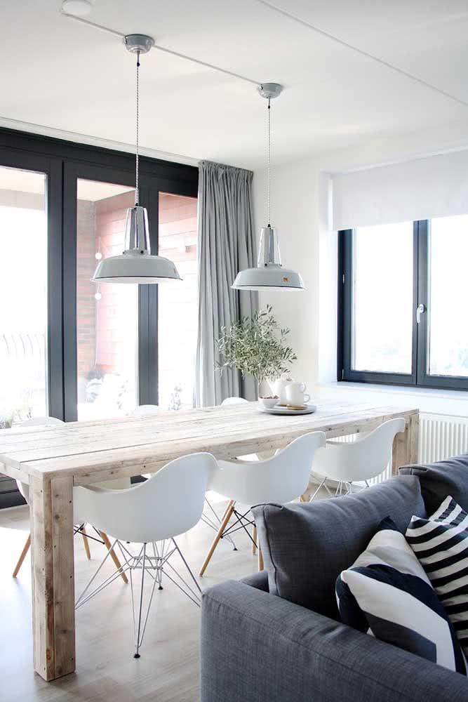 Clean e minimalista, essa mesa de madeira rústica vem acompanhada de cadeiras Eames