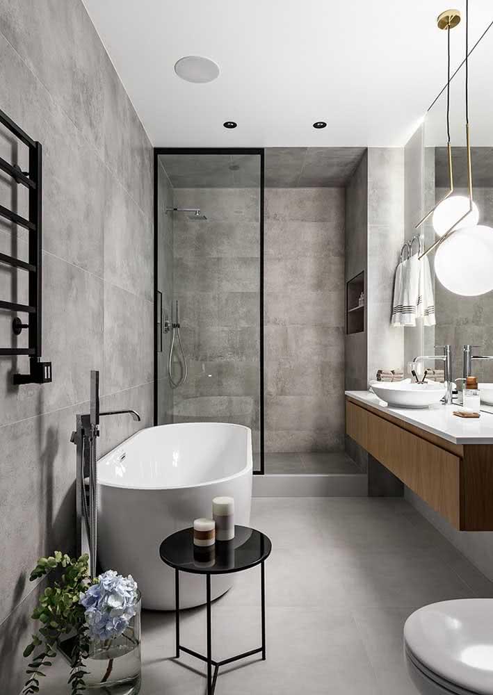 Banheiro moderno com piso e revestimentos cinza. Destaque para os detalhes em preto e em madeira