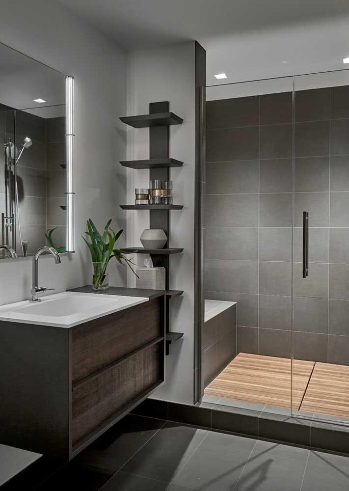 Banheiro cinza com deck de madeira no box