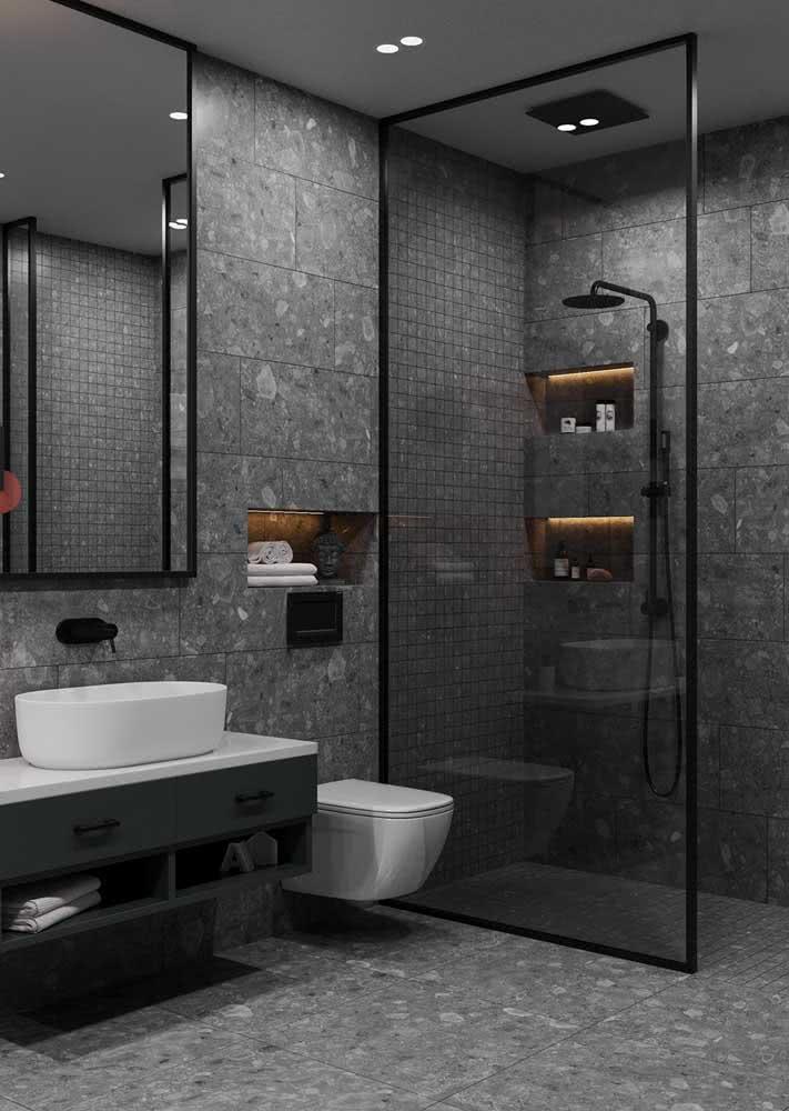 A iluminação indireta traz calor e conforto necessário para o banheiro cinza e preto
