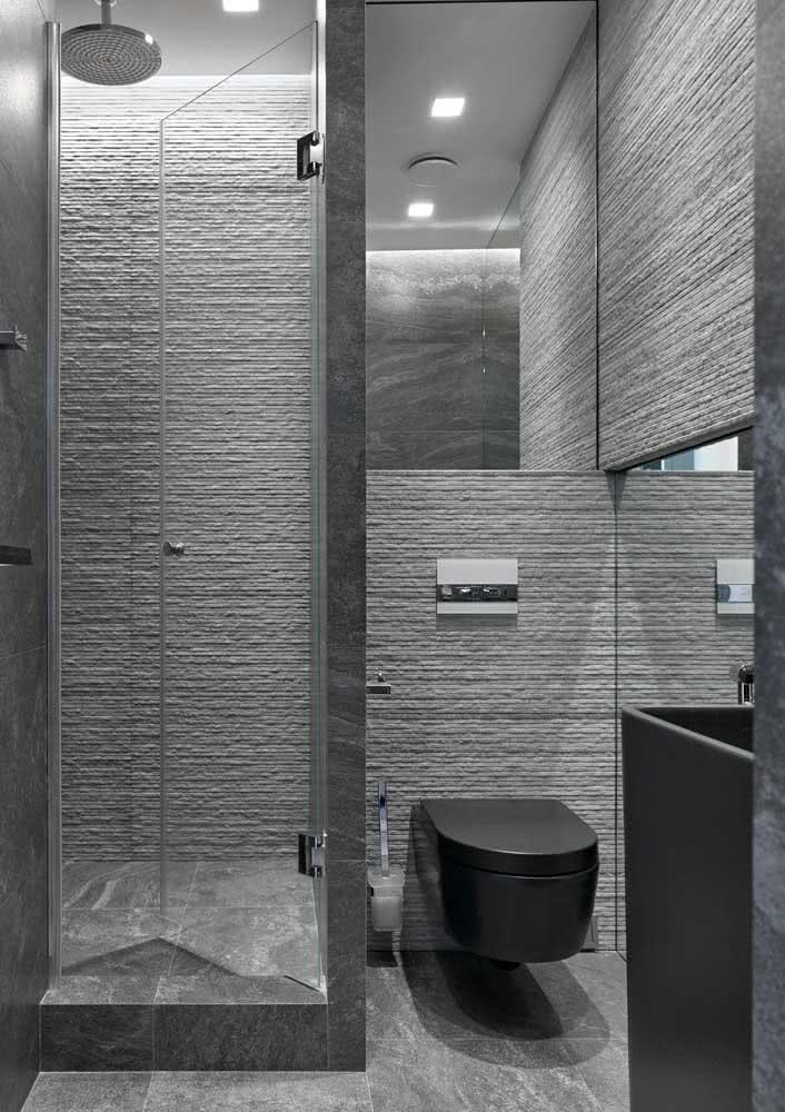 A iluminação valoriza a textura desse banheiro cinza