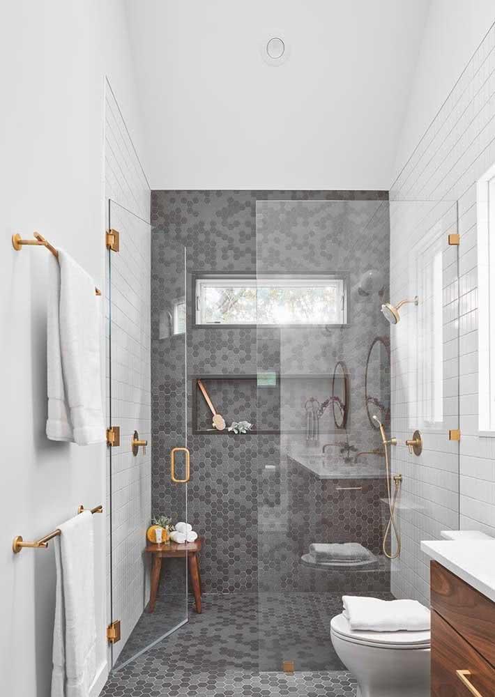 Banheiro com pastilhas cinza usadas na área interna do box e que se estendem para o piso