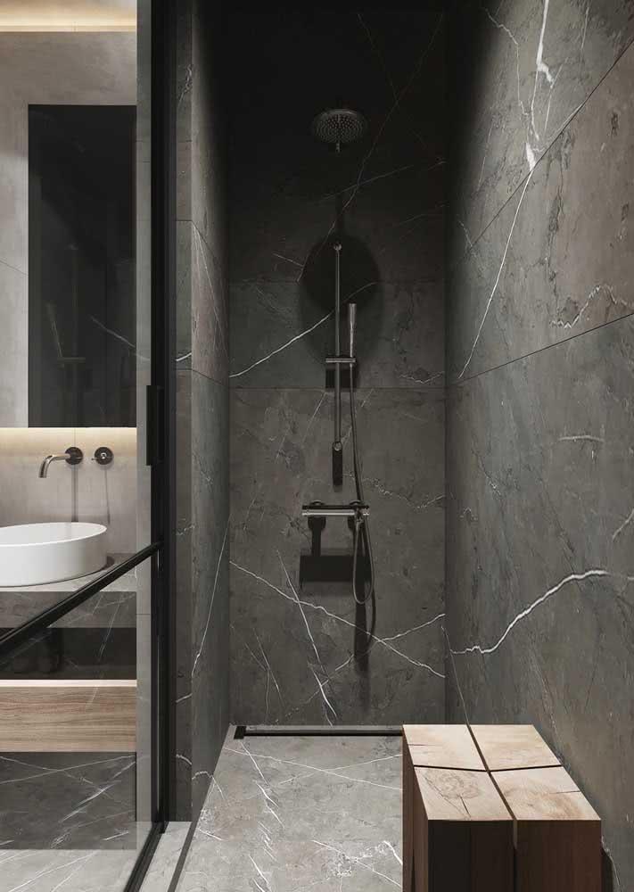 Banheiro cinza moderno com revestimento apenas na área do box