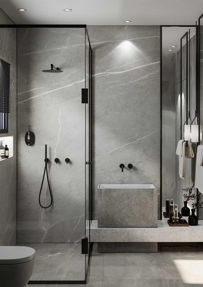 Banheiro com revestimentos cinza na parede e no piso