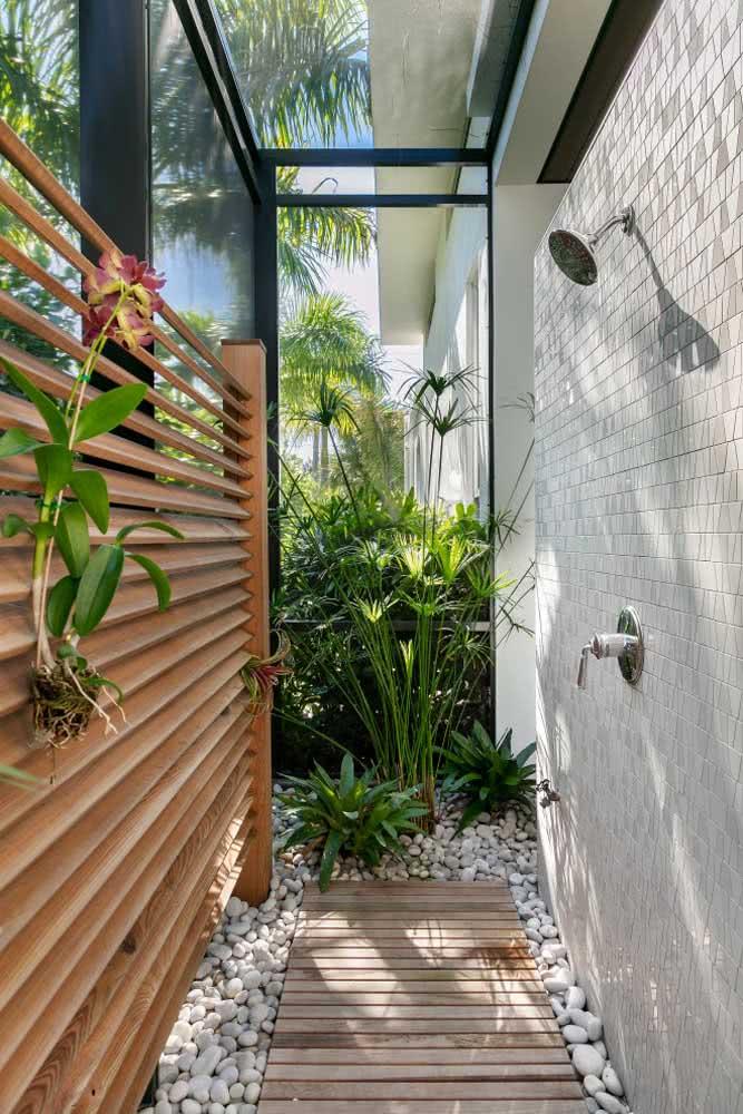 Banheiro ao ar livre decorado com diferentes espécies tropicais