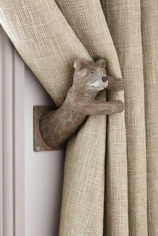 Aqui quem ajuda no trabalho de segurar a cortina é o ursinho de madeira