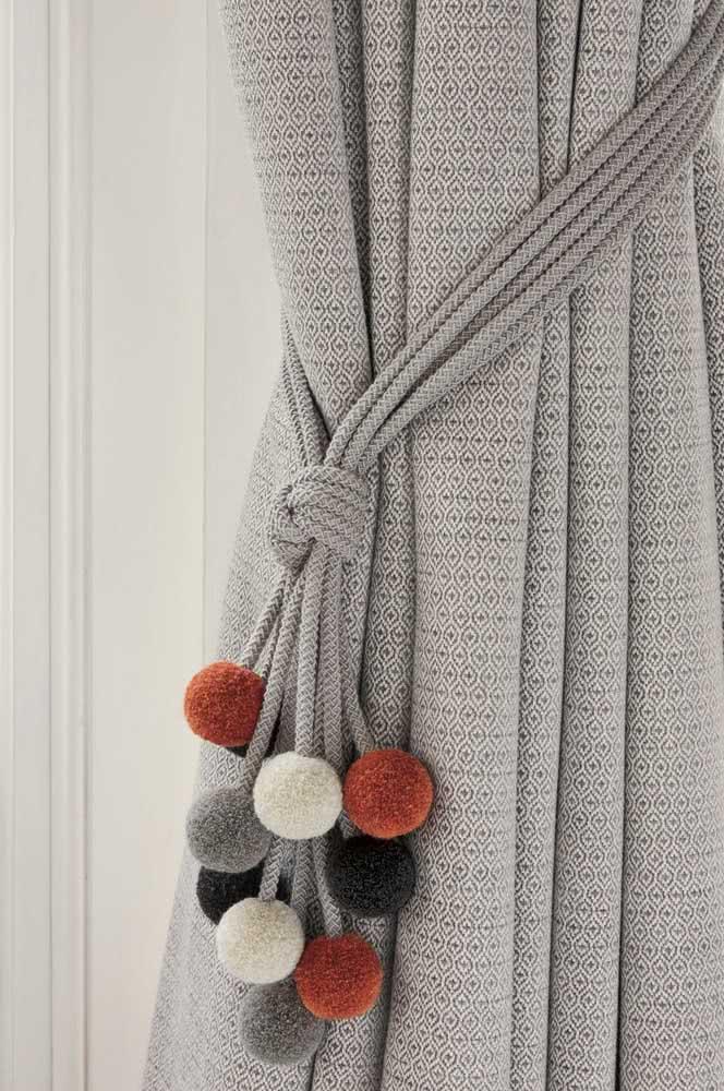 A corda cinza, na cor do tecido da cortina, garantiu todo o destaque para os pompons de lã colorida