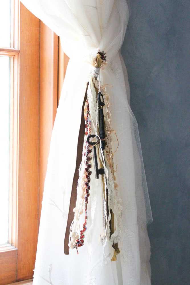 Essa ideia é muito legal: pegue todas as fitas que tiver em casa e use-as como prendedor de cortina