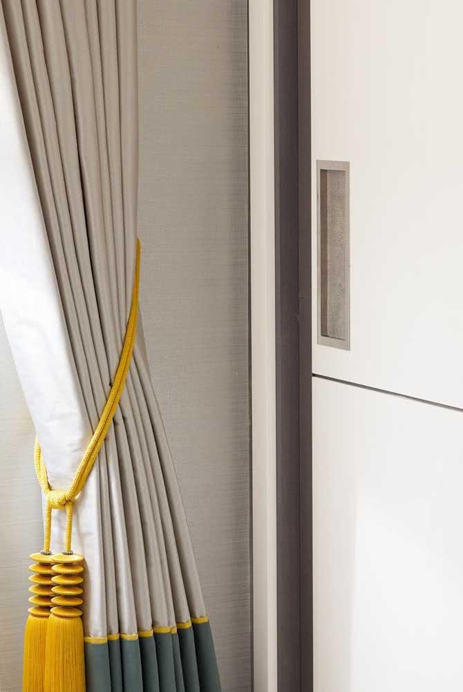 E se o quarto estiver neutro demais, use um prendedor de cortina colorido e alegre