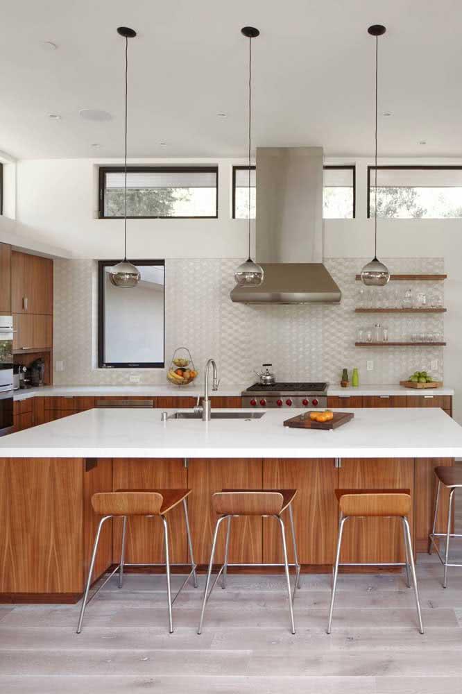 Uma cozinha clean e moderna com armários de madeira e bancadas de pedra