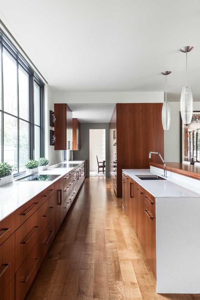 Cozinha com armários de madeira maciça contrastando com a elegante bancada de pedra sintética