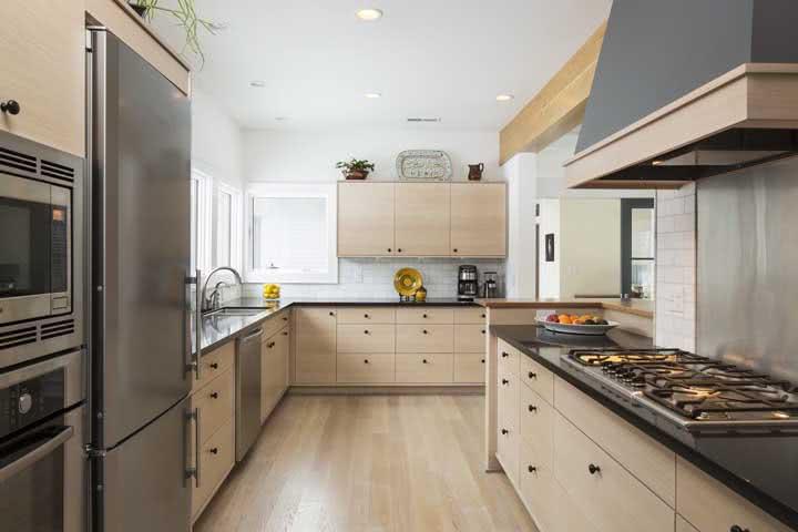 Os puxadores pretos são o diferencial dessa cozinha de madeira