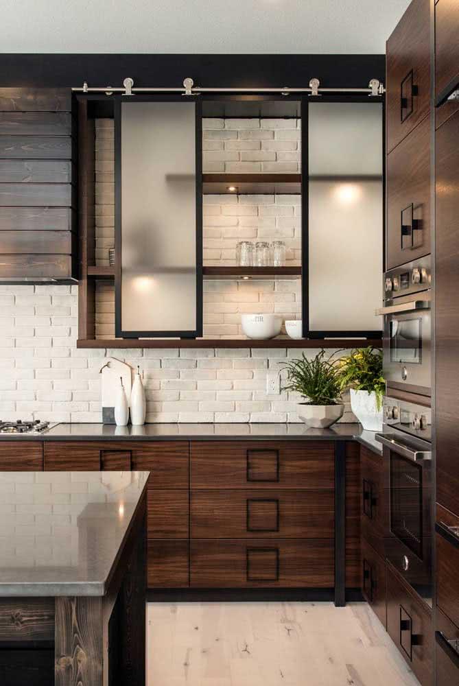 Cozinha de madeira rústica tem parede de tijolinho