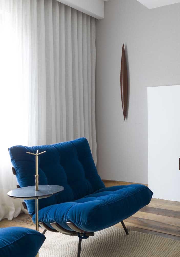 Mas se a intenção é criar contraste, invista em uma poltrona costela azul para a sala branca