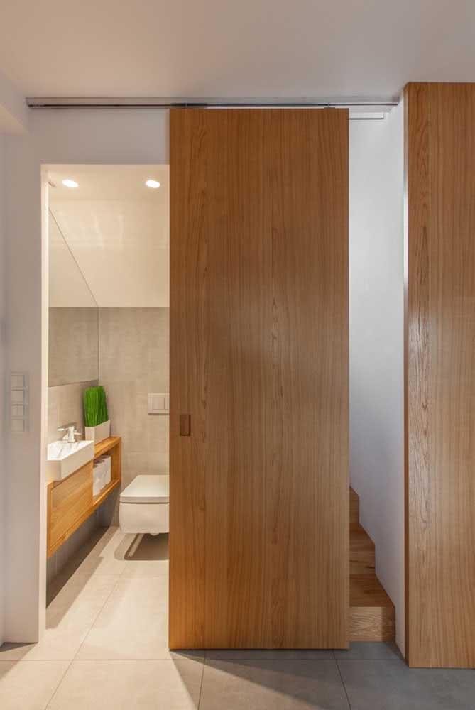 Porta de madeira de correr para o banheiro. Charme e elegância revestindo toda a extensão da parede