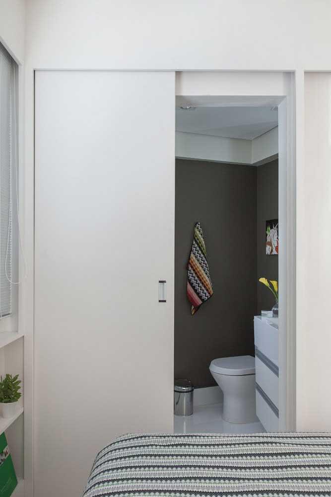 Discreta, essa porta de correr embutida garante a otimização da área do quarto e do banheiro