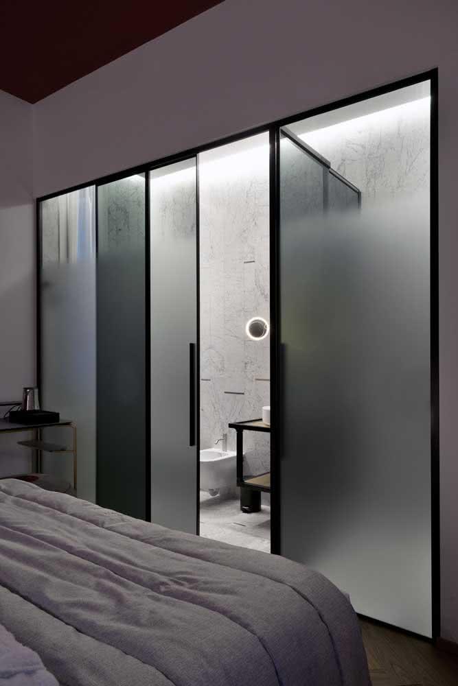 Porta de correr de vidro para o banheiro da suíte. Destaque para o uso do vidro jateado em composição com a esquadria preta