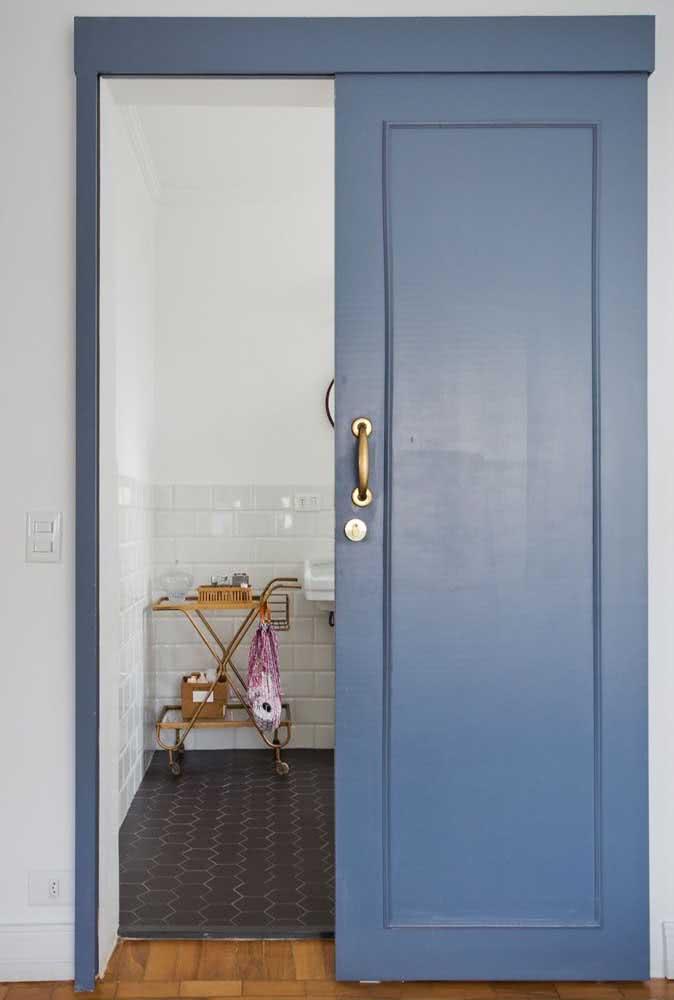 Uma porta de correr azul e com puxador dourado para você cair de amores