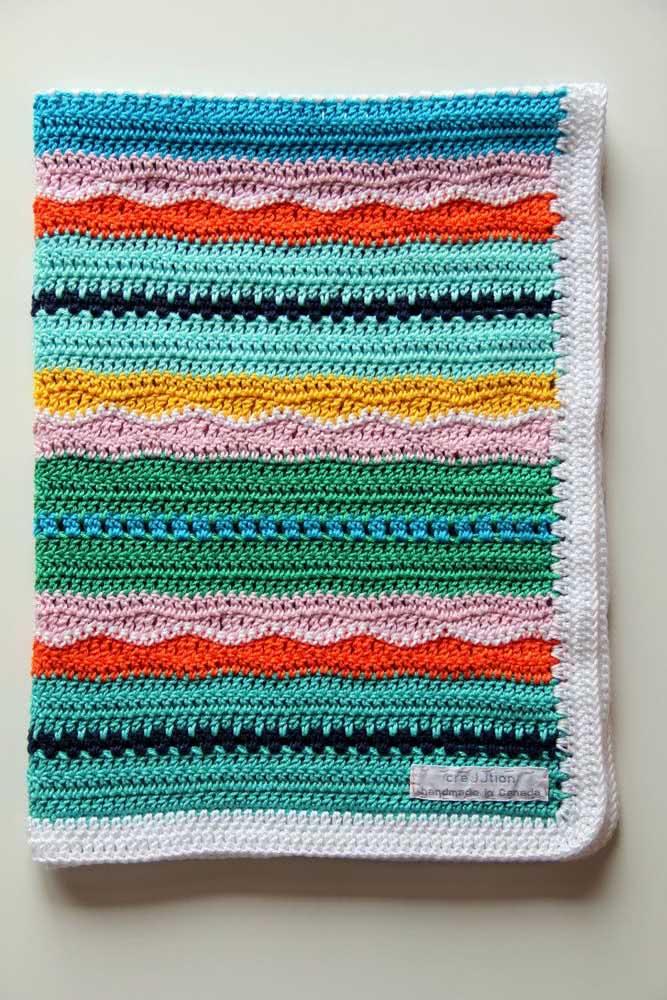 Manta de crochê para bebê com listras coloridas seguindo formatos diferentes