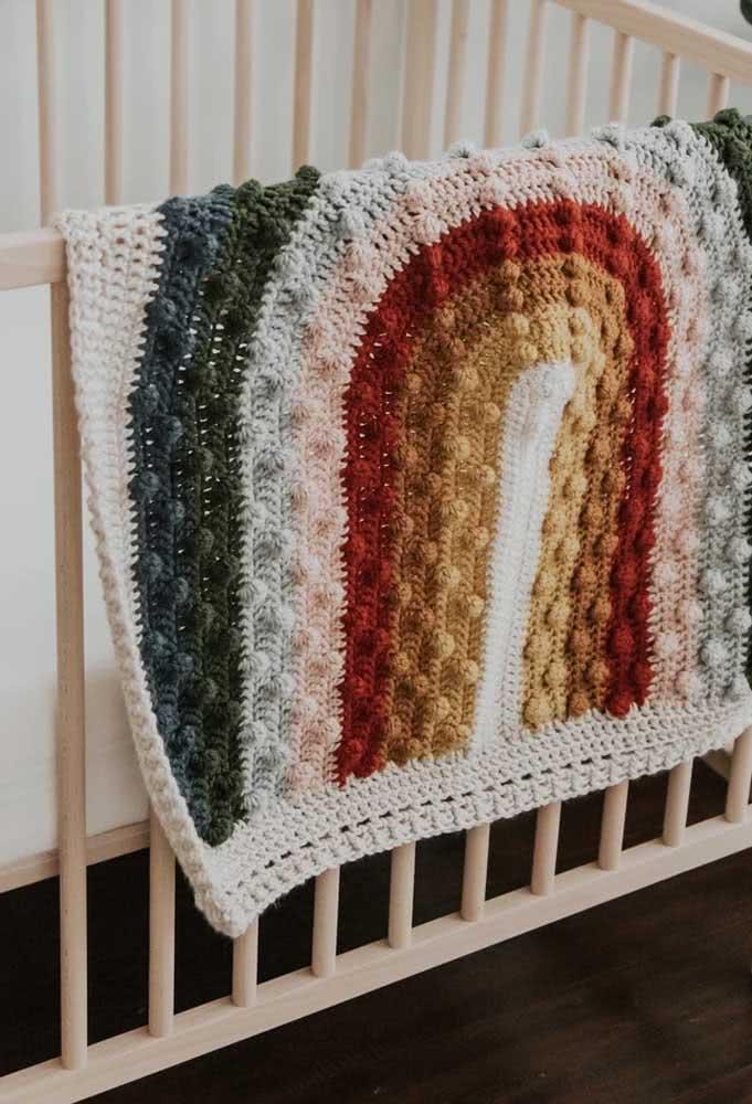 Uma manta de crochê em formato de arco íris para encher o quartinho do bebê de cor e alegria