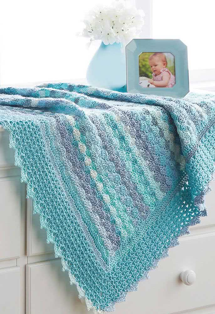 Manta de crochê para bebê menino em degradê de tons de azul. Destaque para a barra da manta que ganhou um trabalho mais delicado de crochê
