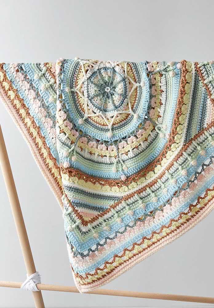 Uma mantinha de crochê nada básica em tons que variam do azul, amarelo, marrom e rosa