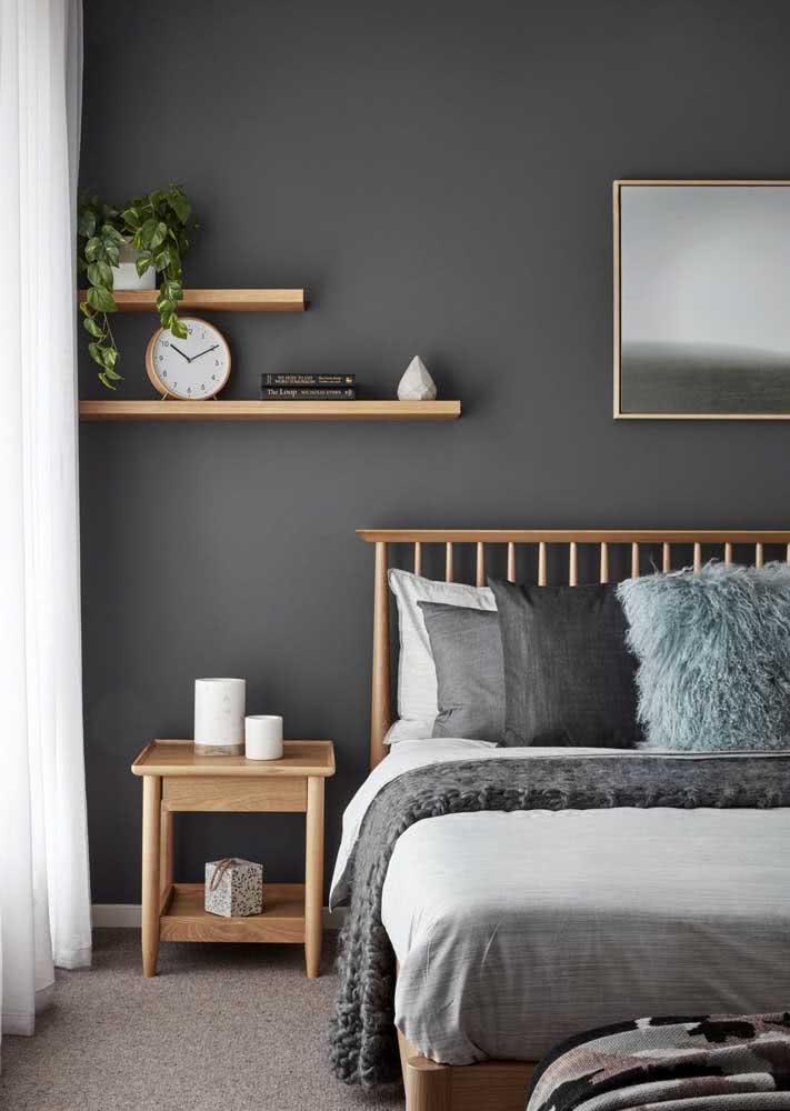 Quarto simples cinza com madeira clara na cama, mesa lateral, prateleiras e até na moldura do quadro.
