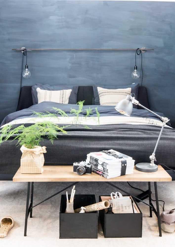 Luminária simples com fio dispostas sobre uma haste de metal sobre a cama de casal.