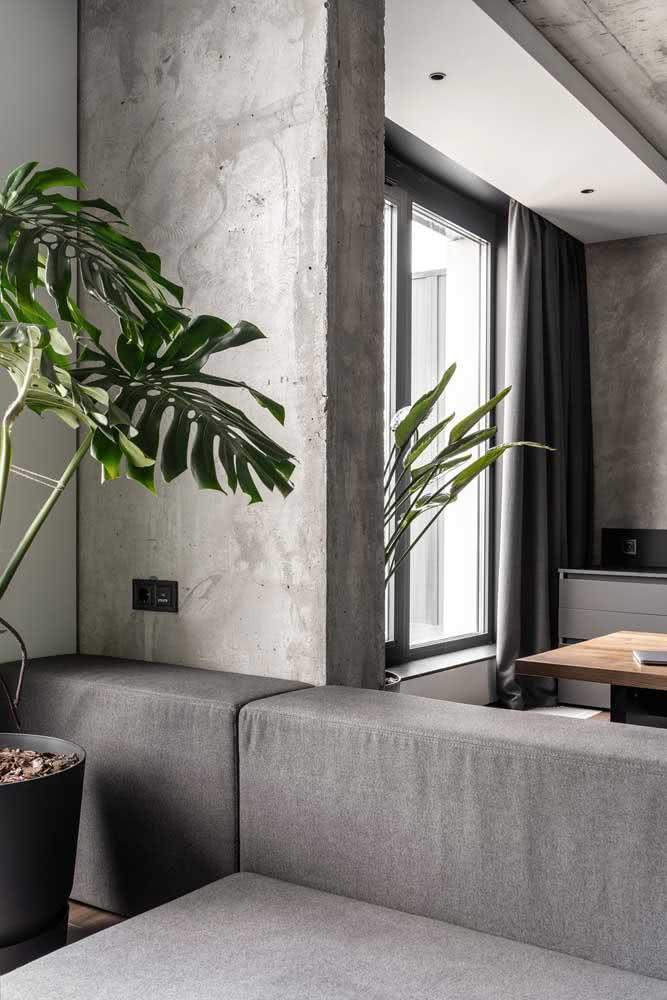 Nesta sala, a textura do concreto aparente traz um clima industrial para o ambiente.