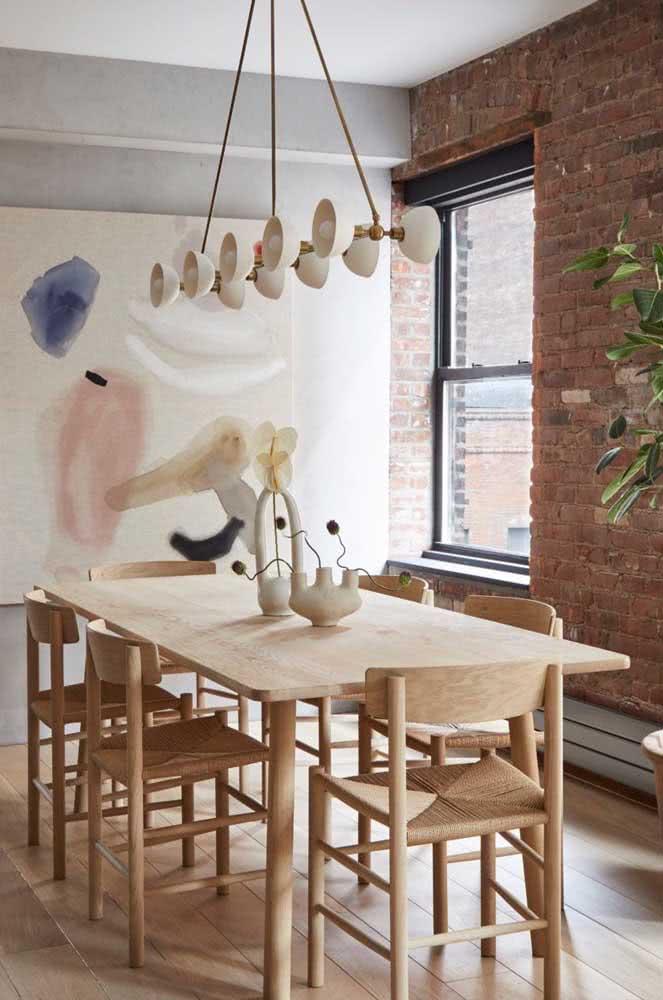 Parede de tijolos aparentes nesta sala de jantar com mesa e cadeiras de madeira.