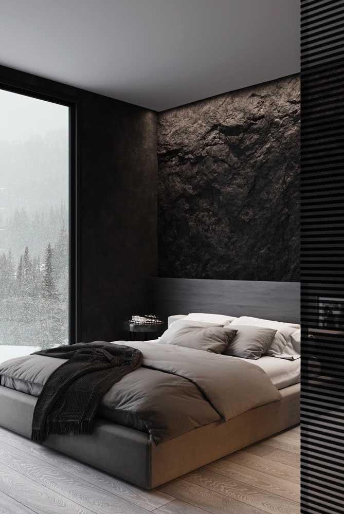 Textura de rocha escura neste quarto de casal aconchegante e intimista.