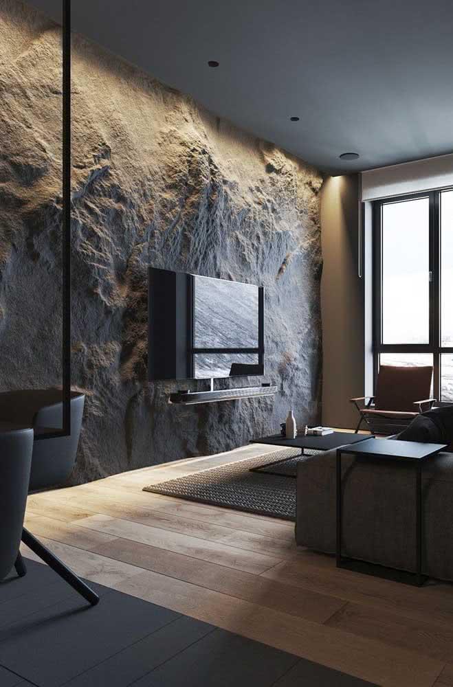 Sala de TV com textura de pedra na parede com iluminação na sanca