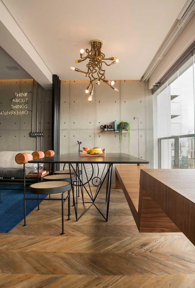 O concreto aparente segue por toda a extensão da parede desse apartamento: da sala até a varanda.
