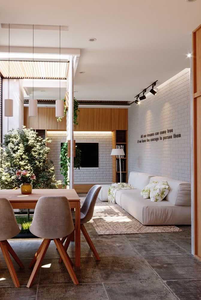 A cor clara do sofá sem braço valoriza a proposta clean e neutra da decoração da sala