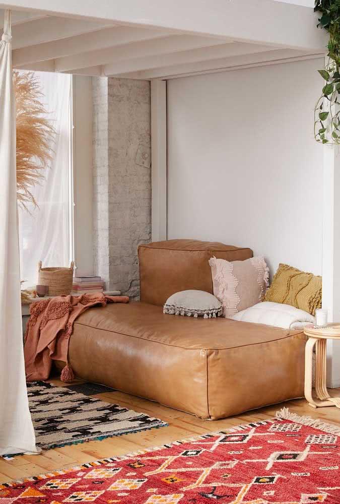 O sofá sem braço dois lugares em couro marrom caiu feito uma luva nessa sala cheia de elementos étnicos