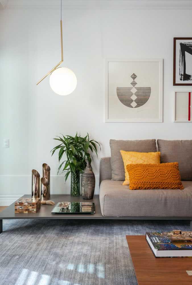 Aqui, o destaque vai para a base embaixo do sofá sem braço cinza que serve como mesinha de apoio