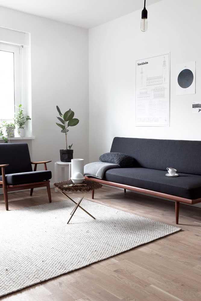 Um sofá sem braço simples, mas que se torna elegante graças ao tecido preto