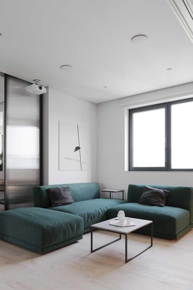 Para sair da neutralidade do branco e preto, invista em um sofá sem braço verde escuro