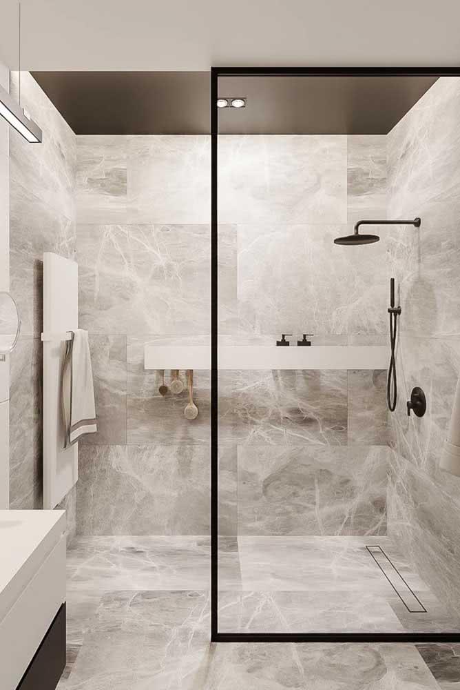 Porcelanato retificado marmorizado no piso e nas paredes desse banheiro