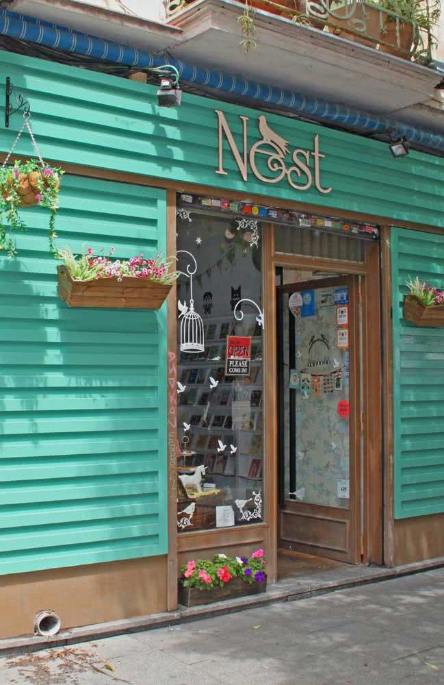 Fachada de loja bonita e barata. Aqui quem se destaca é o painel metálico e as floreiras