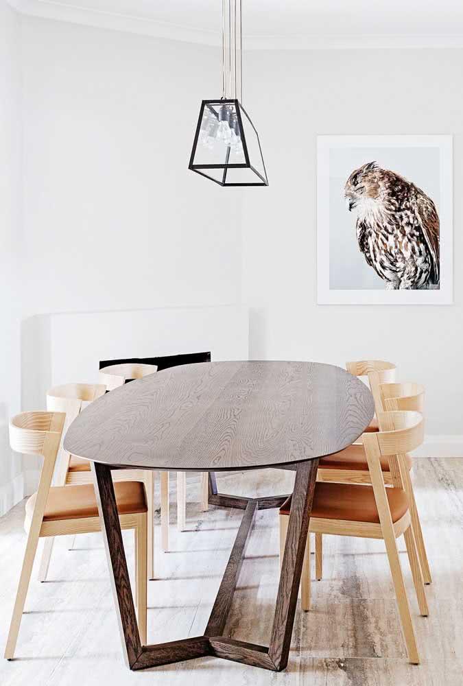Mesa oval de madeira escura em contraste e harmonia com as cadeiras de tom claro
