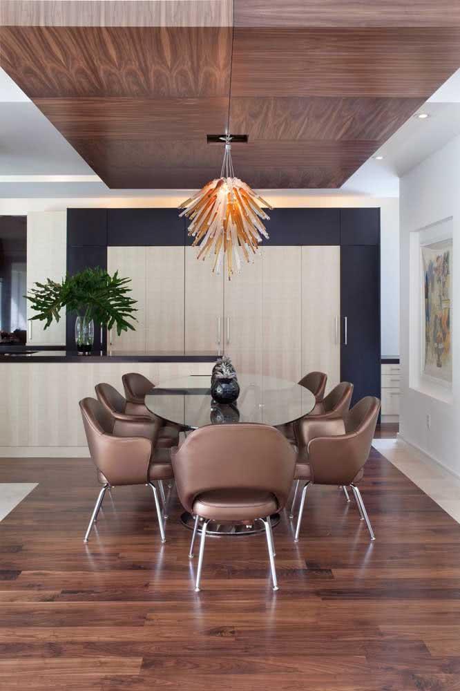 Um luxo essa mesa oval com tampo de vidro fumê acompanhada pelas cadeiras de couro