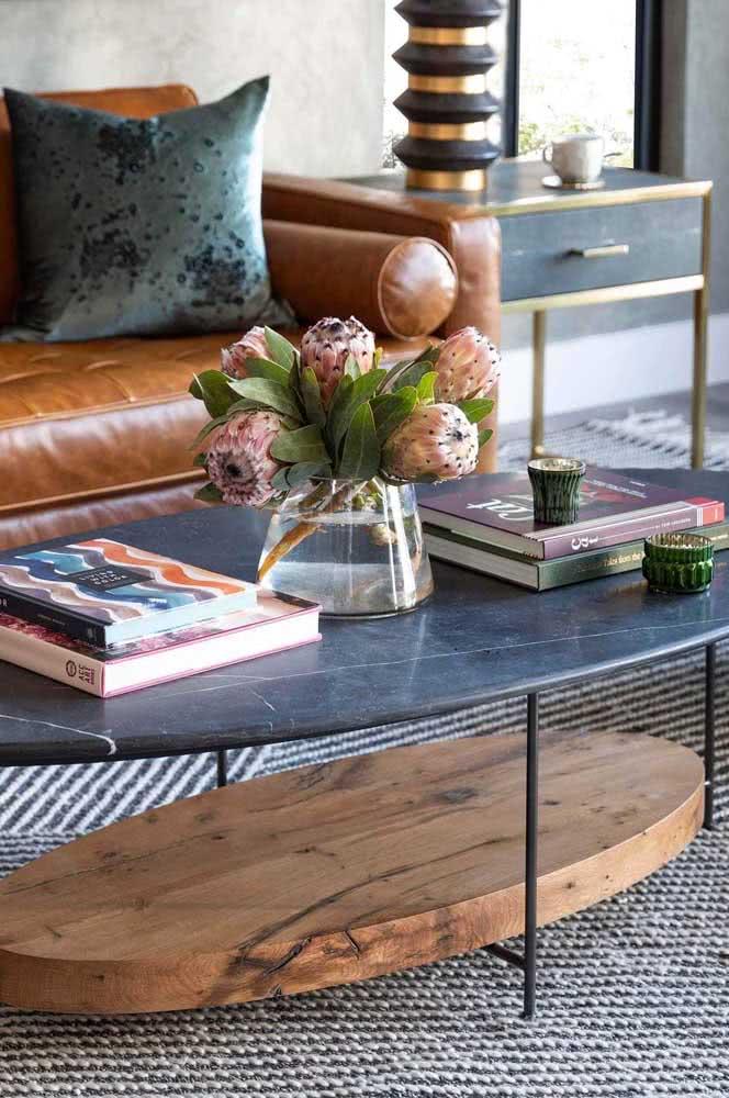 O destaque dessa mesa oval de centro é o mix de materiais
