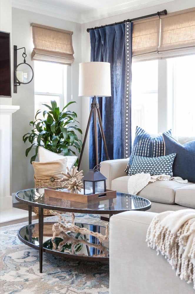 Na sala de estar, a mesa oval de vidro é perfeita para expor os objetos decorativos