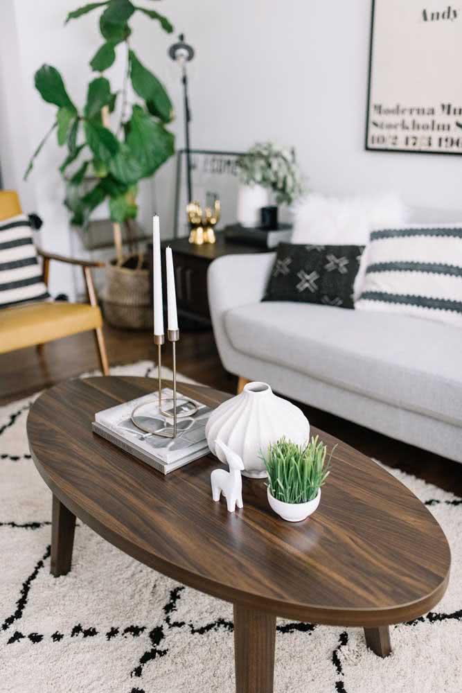 Mesa oval simples de madeira, mas super funcional na sala de estar
