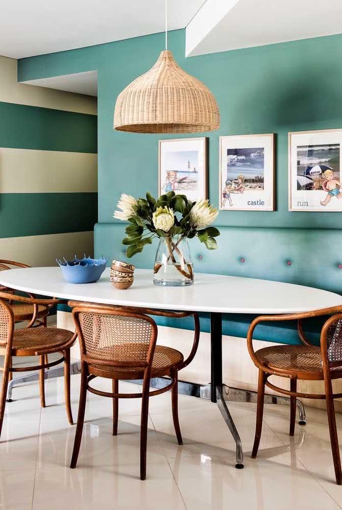 As cadeiras de palhinha dão um toque descontraído para a mesa oval