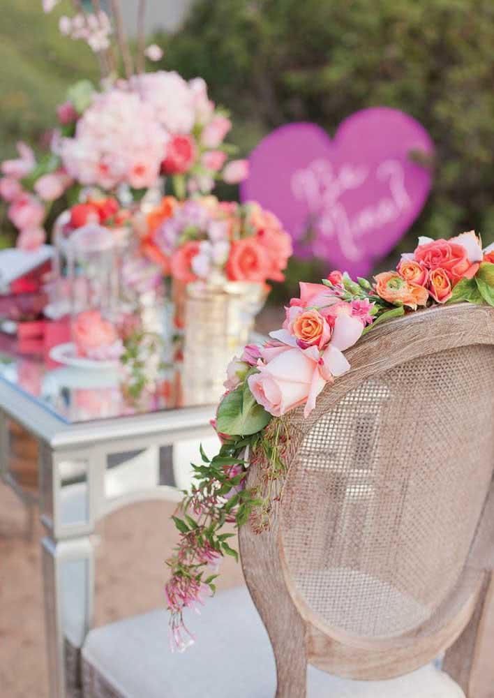 Jantar romântico ao ar livre decorado com muitas flores