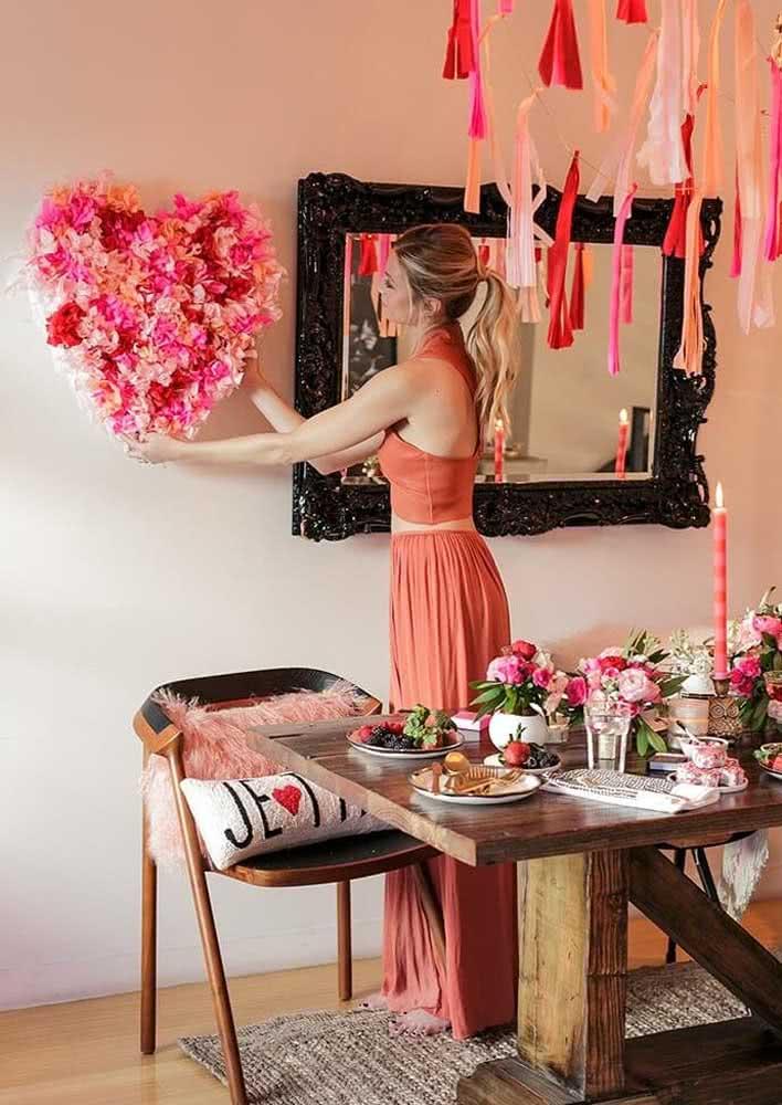 Jantar romântico de dia dos namorados decorado com arranjos de flores simples. Destaque para o coração na parede feito com pedaços de papel