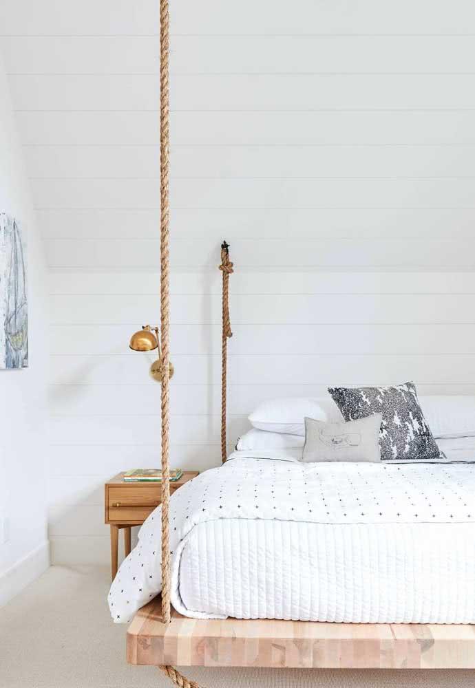 Quarto clean e iluminado com cama flutuante suspensa por cordas