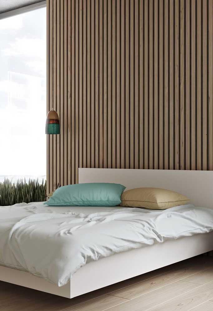 Aqui, a cama flutuante branca foi valorizada pelo painel ripado de madeira